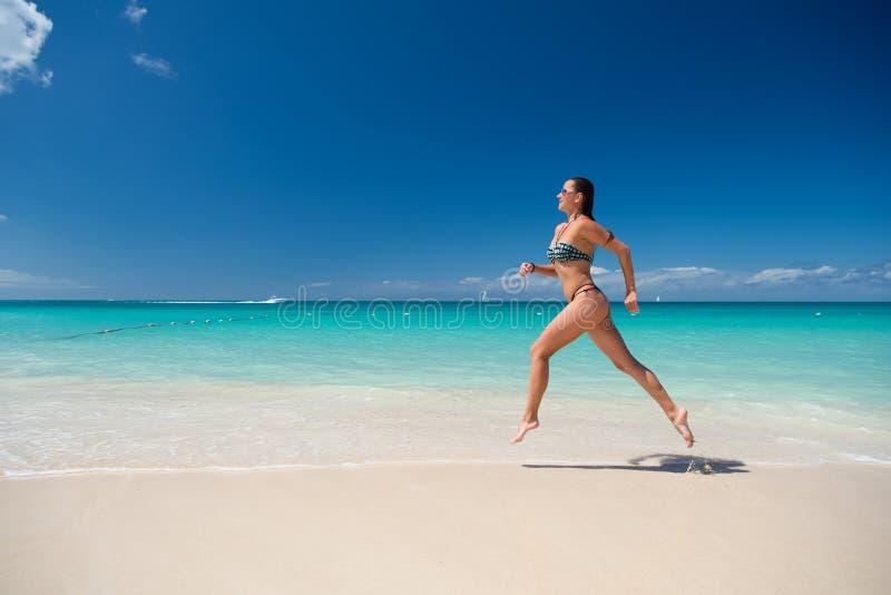 Mädchen im Schwimmenbikini, der auf Sandstrand läuft lizenzfreies stockbild