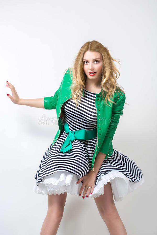 Mädchen im sich entwickelnden Kleid und in der grünen Jacke stockfoto