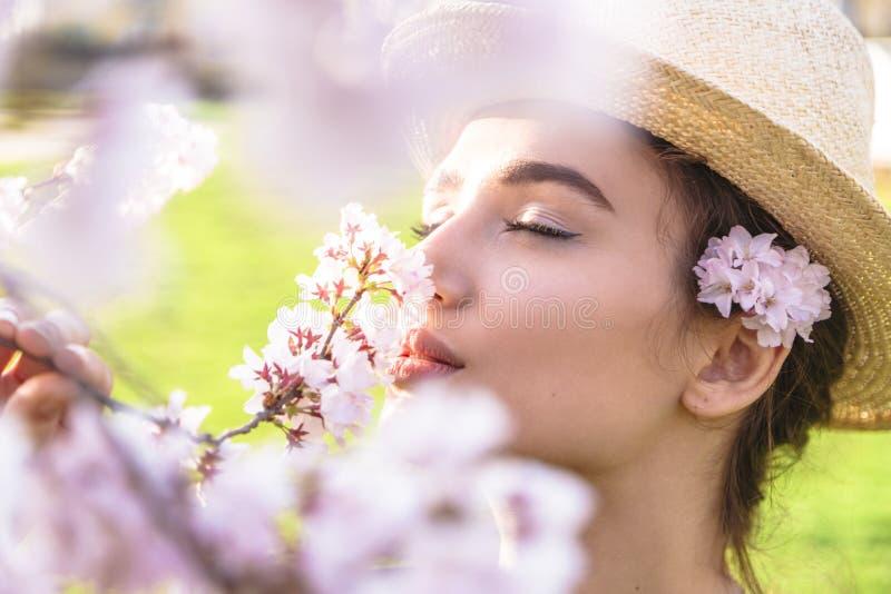 Mädchen im Strohhut mit Blumen hinter dem Ohr im Freien stockfotografie
