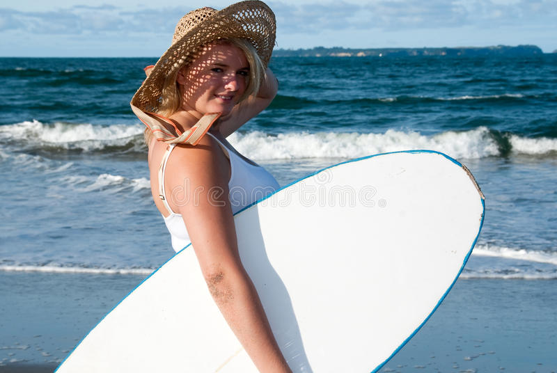 Mädchen im sunhat mit Surfbrett stockfotografie