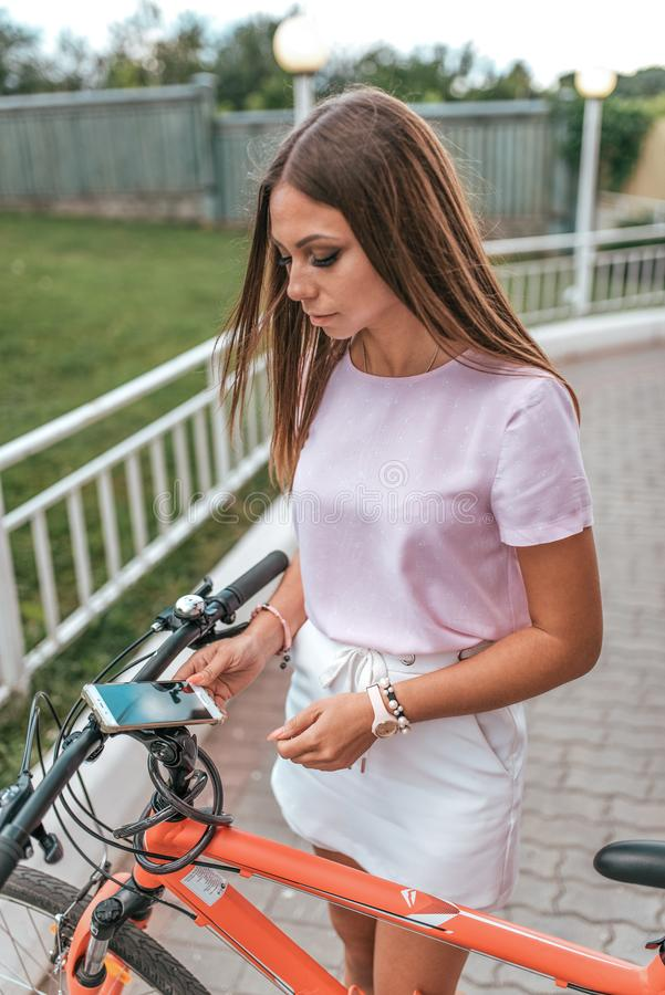 M?dchen im Telefon der Sommerstadt in der Hand, Wahl des Weges, Parkfahrrad r Fahrradaktivierung lizenzfreie stockbilder