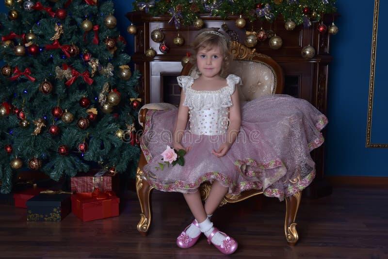 Mädchen im Weiß mit dem rosa Kleid, das im Stuhl nahe Weihnachten tr sitzt lizenzfreies stockfoto