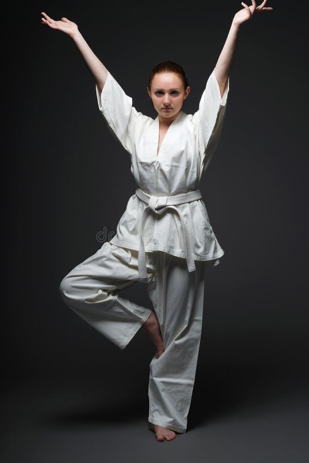 Mädchen im weißen Kimono, der in der traditionellen Haltung steht stockfotografie