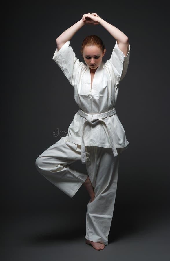 Mädchen im weißen Kimono, traditionelle Position von Aikido lizenzfreie stockbilder