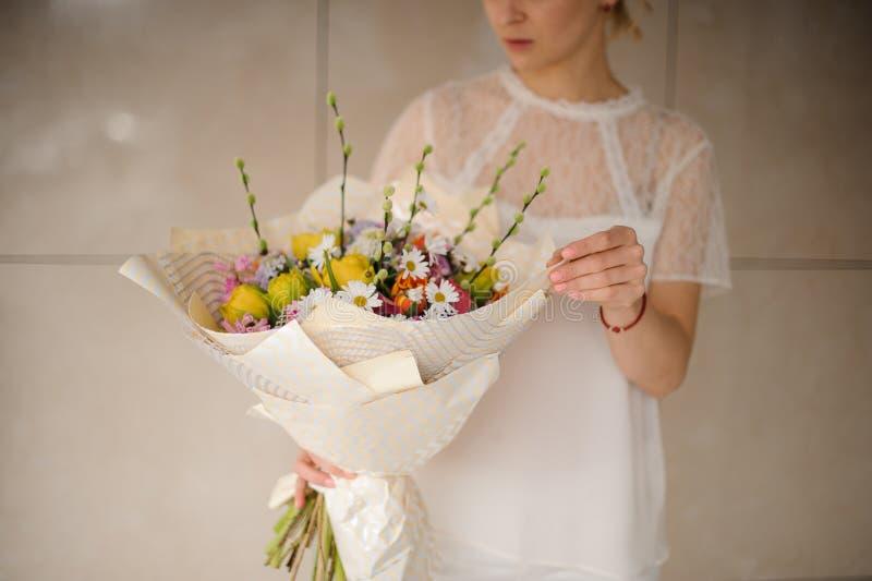 Mädchen im weißen Kleid, das einen Frühlingsblumenstrauß von zarten verschiedenen Farbblumen hält stockfoto