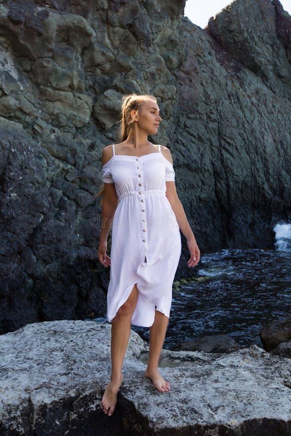 Mädchen im weißen Kleid, das gegen Küstenfelsen aufwirft stockfotos