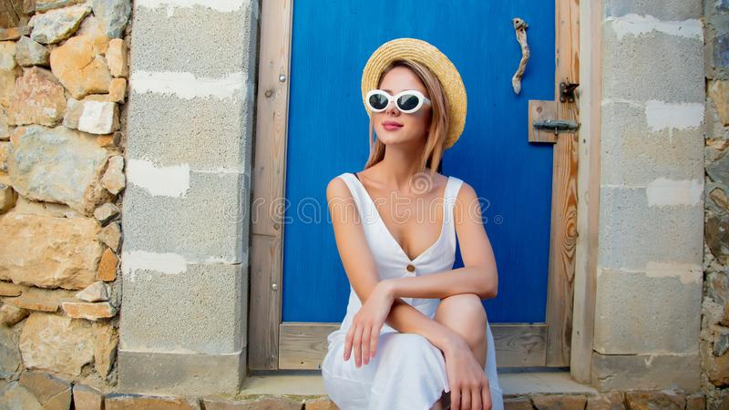 Mädchen im weißen Kleid, das nahe einem alten Haus sitzt stockfoto