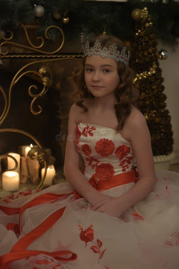 Mädchen im weißen Kleid mit roten Blumen, Kamin mit brennenden Kerzen lizenzfreies stockbild