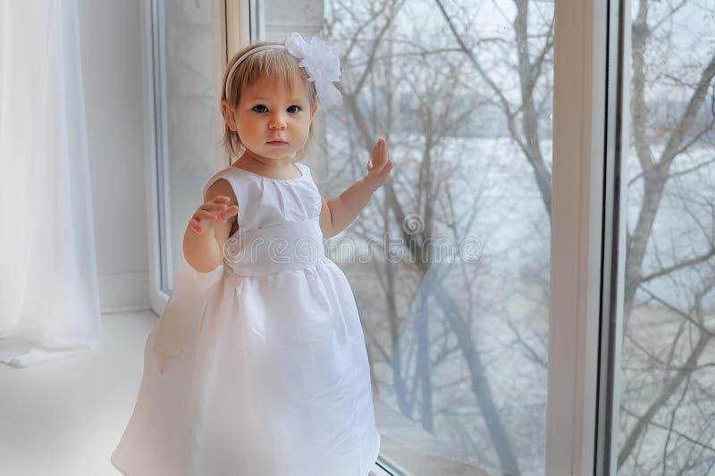 Mädchen im weißen Kleid nahe bei einem großen Fenster lizenzfreie stockfotografie