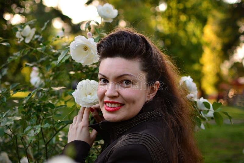 Mädchen im Weißrosengarten (Porträt der jungen Frau) lizenzfreie stockfotos