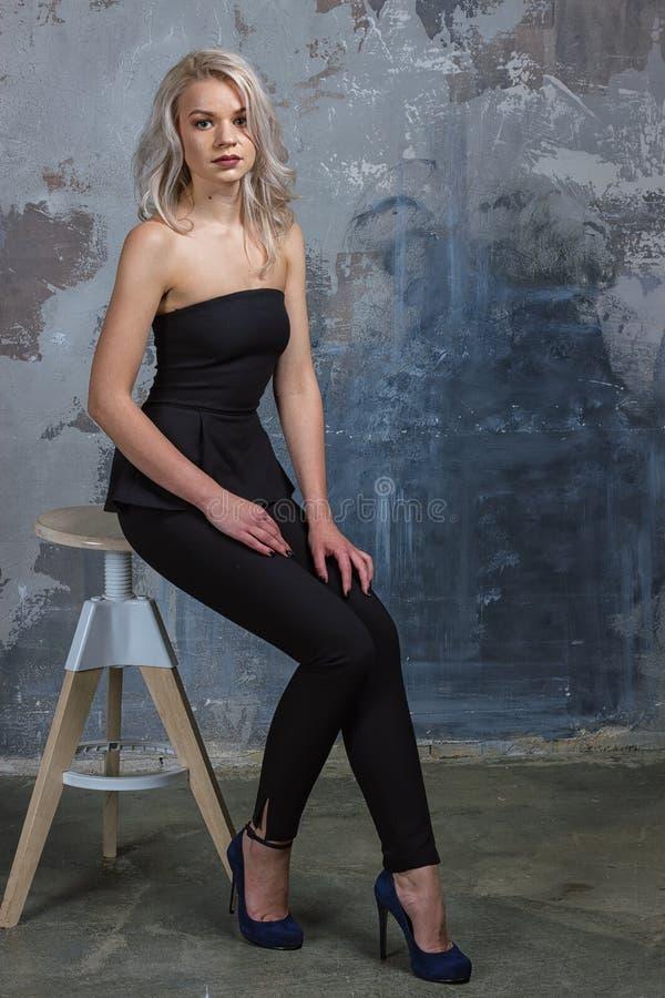 Mädchen ir, das auf einem Hochstuhl nahe bei einer Wand sitzt lizenzfreie stockfotos