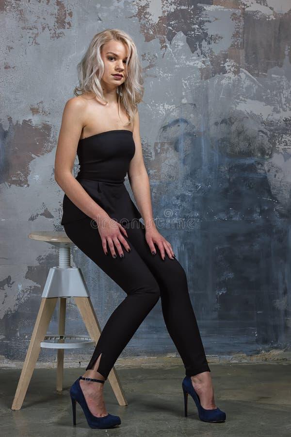Mädchen ir, das auf einem Hochstuhl nahe bei einer Wand sitzt lizenzfreies stockfoto