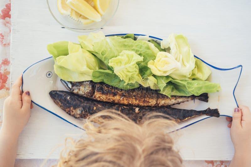 Mädchen isst gegrillte Fische auf der Platte stockfoto