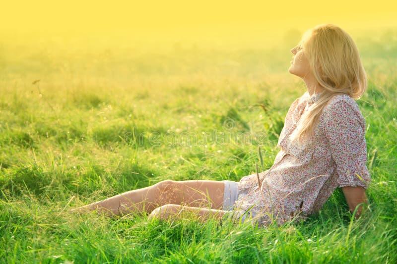 Mädchen ist auf grünem Feld entspannend stockfoto