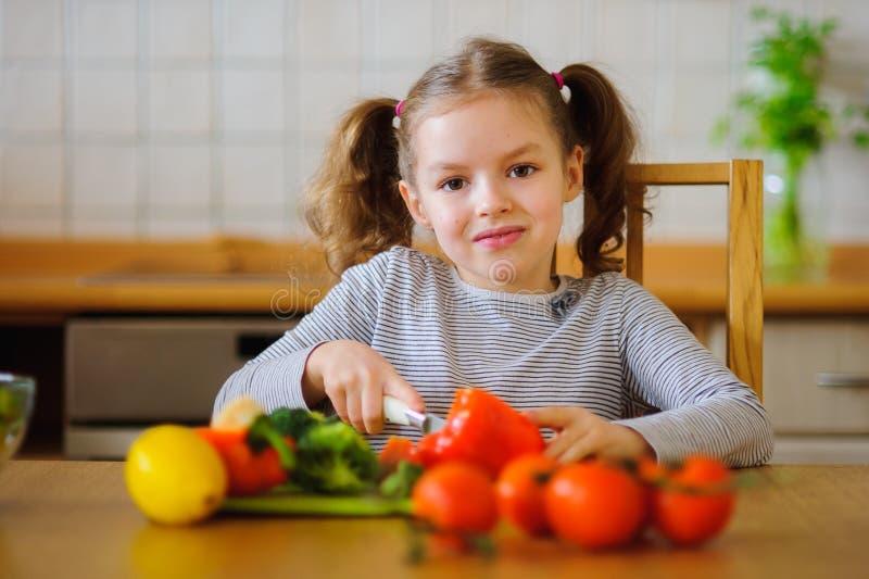 Mädchen 8-9 Jahre alt in der Küche, die Gemüse für einen Salat schneidet lizenzfreie stockfotos