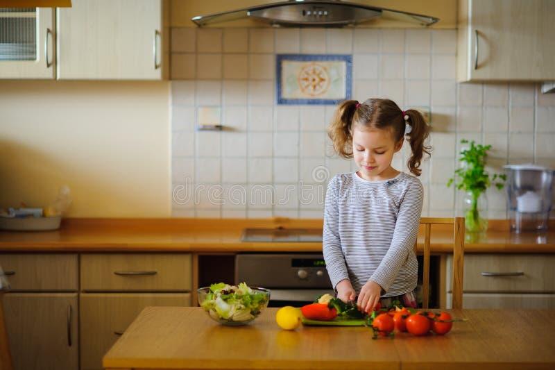 Mädchen 8-9 Jahre alt in der Küche, die Gemüse für einen Salat schneidet lizenzfreie stockbilder