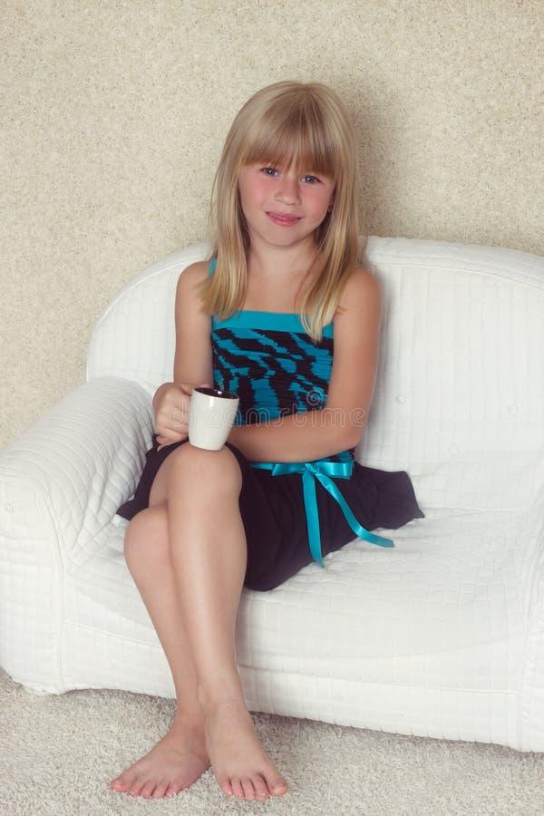 Mädchen 5 Jahre alte Sitzen auf einem Sofa mit Schale lizenzfreie stockfotografie