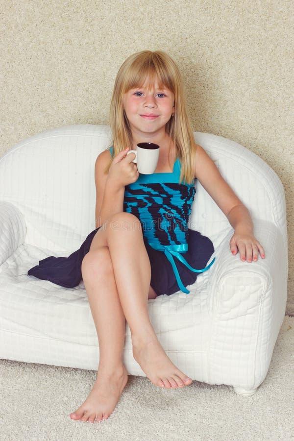 Mädchen 5 Jahre alte Sitzen auf einem Sofa mit Schale stockbilder