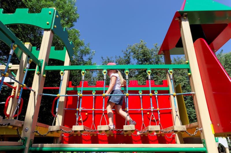 Mädchen 6 Jahre geht, indem sie eine horizontale Leiter auf dem Spielplatz hängt lizenzfreie stockfotografie