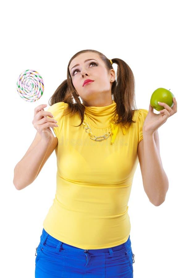 Mädchen-Jugendlicher mit Apfel und Süßigkeit lizenzfreie stockbilder