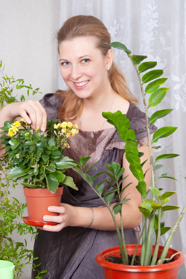 Mädchen kümmert sich um Blumen lizenzfreie stockbilder