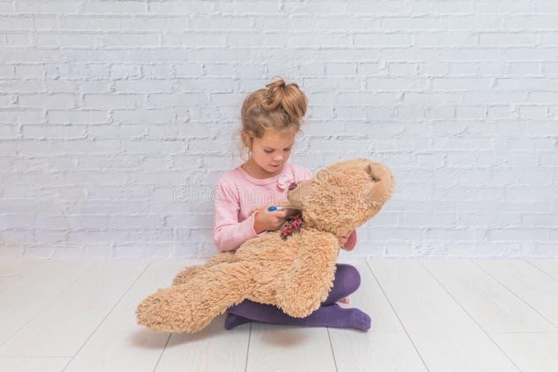 Mädchen, Kind misst die Temperatur eines Spielzeugbären, gegen ein wh lizenzfreie stockbilder