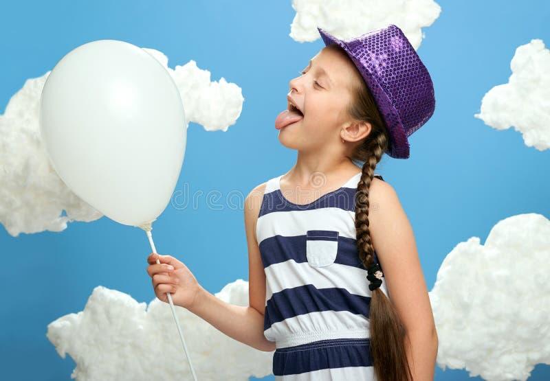 Mädchen kleidete in gestreiftem Kleid und im Farbhut an, die auf einem blauen Hintergrund mit Baumwollwolken, weißer Luftballon,  lizenzfreie stockfotografie