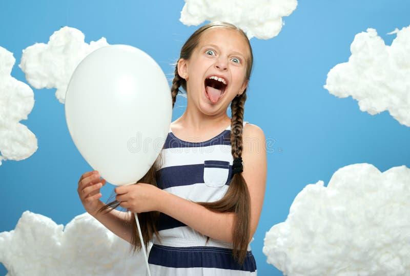 Mädchen kleidete im gestreiften Kleid an, das auf einem blauen Hintergrund mit Baumwollwolken, weißem Luftballon, dem Konzept des stockfoto