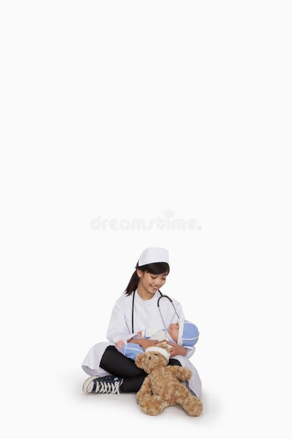 Mädchen kleidete oben als Doktor mit Teddybären und Puppe an lizenzfreie stockfotos