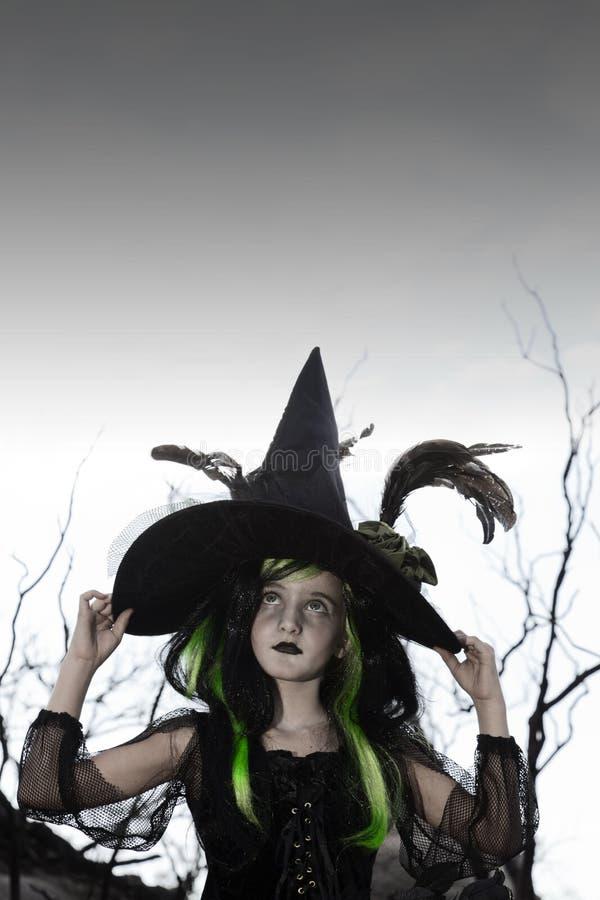 Mädchen kostümiert als Hexe, die schaut, hochhalten ihren Hut lizenzfreie stockbilder