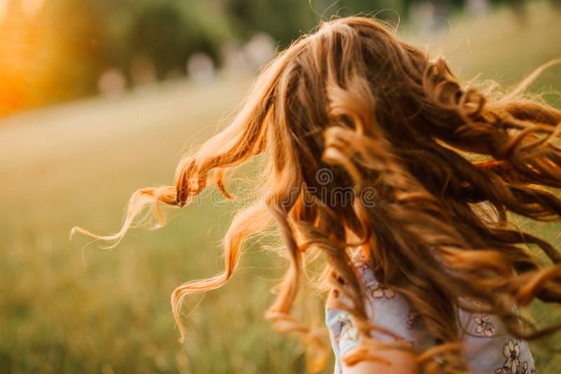 Mädchen lässt Haarlocken entwickeln Glühensonne laufen stockfoto