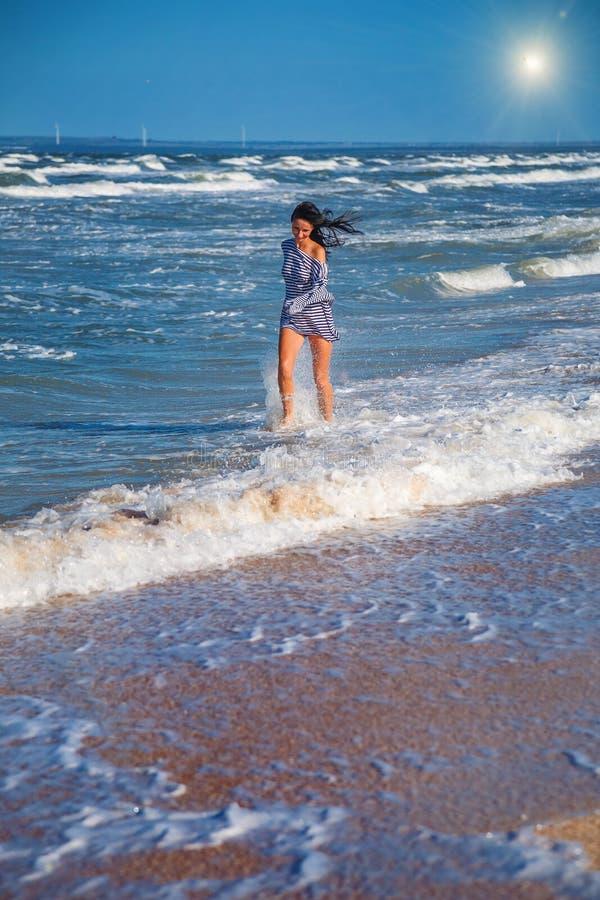Mädchen läuft entlang den Strand in den Wellen, glückliche Stimmungslage lizenzfreie stockfotografie