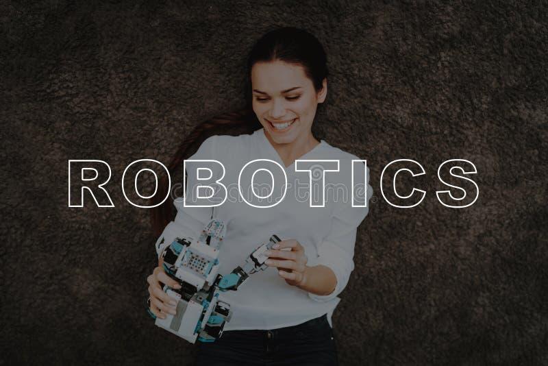 Mädchen lügen Gray Floor Roboter-Nashorn tablette Spiel lizenzfreie stockfotografie