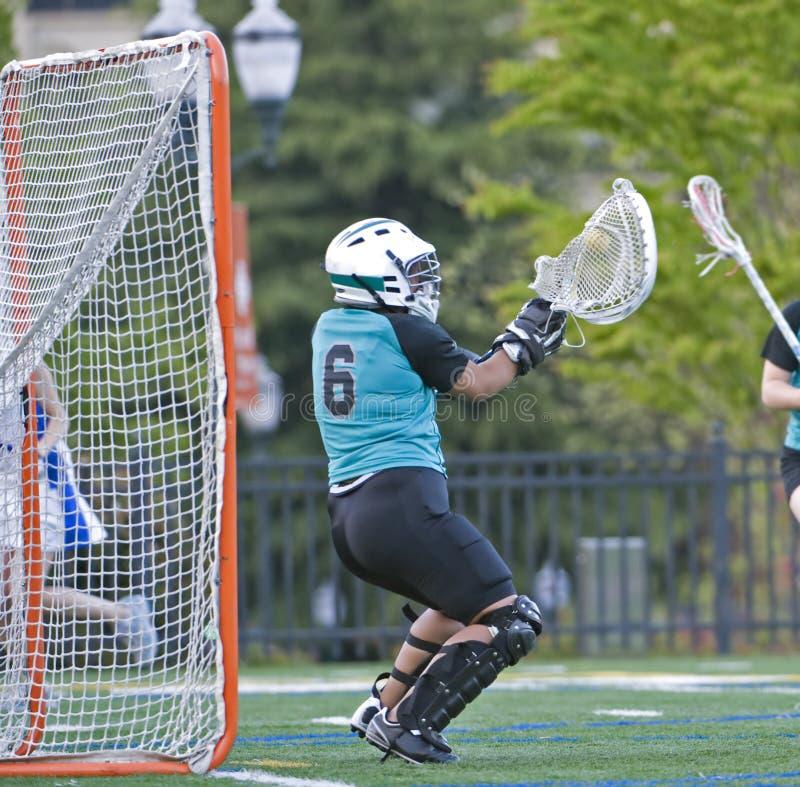 Mädchen Lacrosse, der die Kugel blockt lizenzfreie stockfotografie