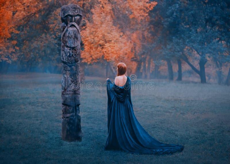 Mädchen in langem blauem s-Kleid mit bloßen Schultern geht in nebelhafte Waldfrauenberufungen, übernatürlichen Dunkelheit zur aus stockbilder