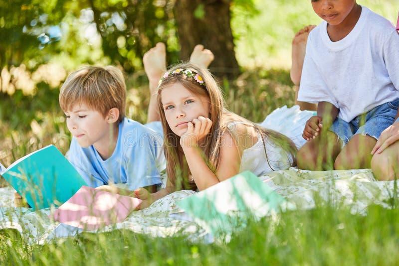 Mädchen langweilt sich beim Lernen im Park stockbild