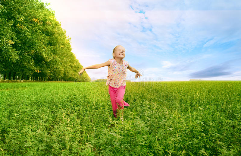 Mädchen laufen gelassen auf grünes Feld lizenzfreie stockfotografie