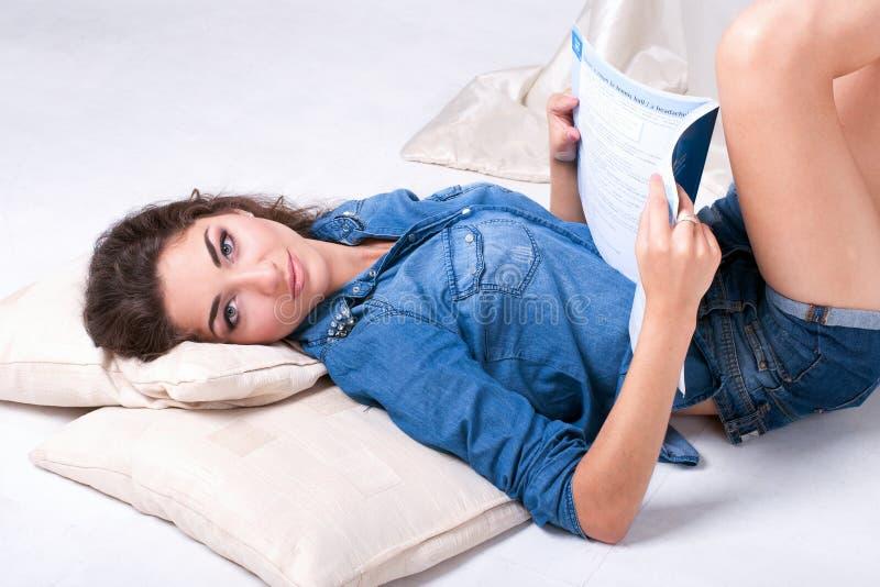 Mädchen legt auf den Boden und liest das Buch stockbild
