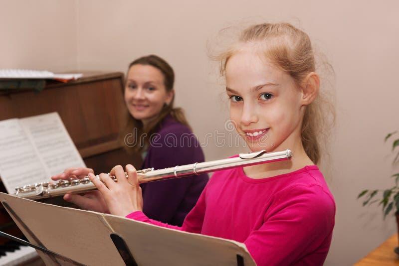 Mädchen, Lehrer und Flöte, Klavier stockfotografie