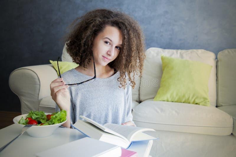 Mädchen-Lesebuch des gelockten Haares jugendlich und essen Salat stockbilder