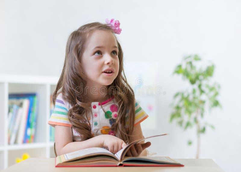 Mädchen-Lesebuch des Vorschülers intelligentes beim Sitzen auf Stuhl in der Kindertagesstätte stockfotografie