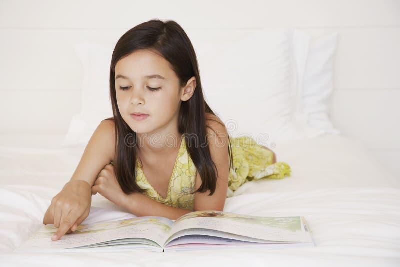 Mädchen-Lesegeschichten-Buch im Bett lizenzfreie stockbilder