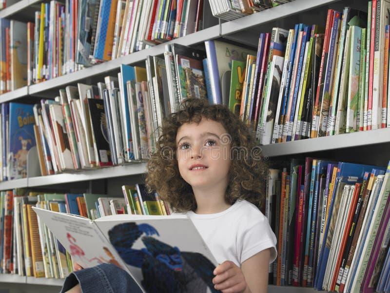 Mädchen-Lesemärchenbuch in der Bibliothek stockfotos