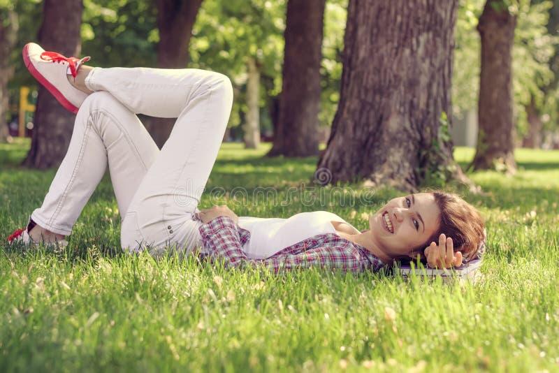 Mädchen liegt auf dem Gras im Park stockfotos