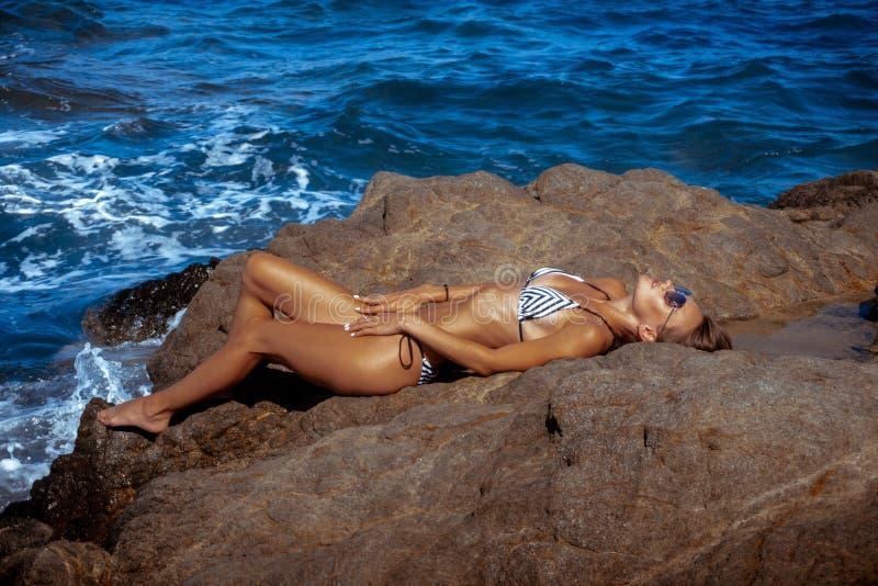Mädchen liegt auf den Felsen durch das Meer stockfoto