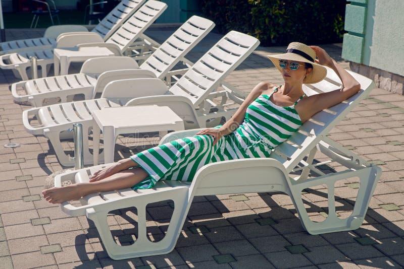 Mädchen liegt auf einem Liege in einem grünen gestreiften Kleid lizenzfreies stockbild