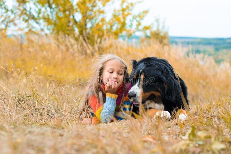 Mädchen liegt nahe bei großem Hund Berner Sennenhund lizenzfreies stockbild