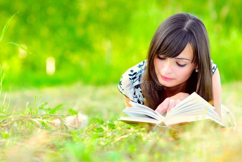 Mädchen liest Buch auf Wiese stockfotografie