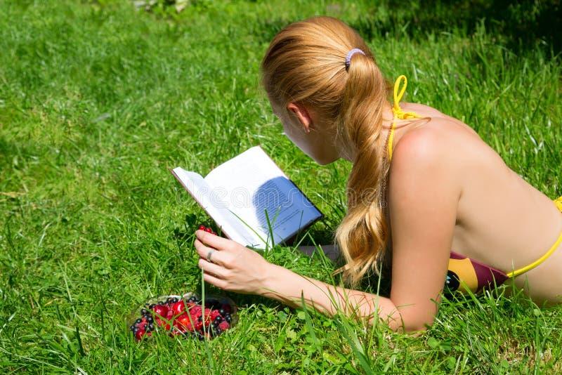 Mädchen liest ein Buch auf dem grünen Gras stockbilder