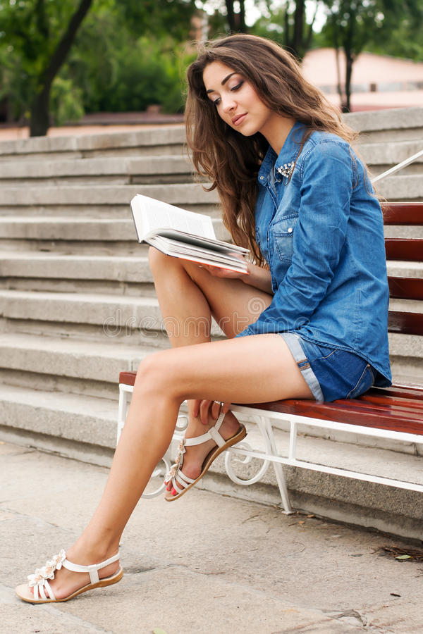 Mädchen liest ein Buch beim Sitzen auf einer Bank gegen das backgroun lizenzfreie stockbilder